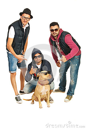 Funky rappers pointing to their pitbull dog