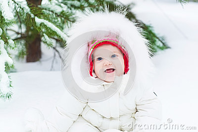 Funny baby girl in snow under Christmas tree