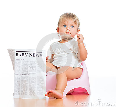 Funny baby sitting on chamberpot with newspaper