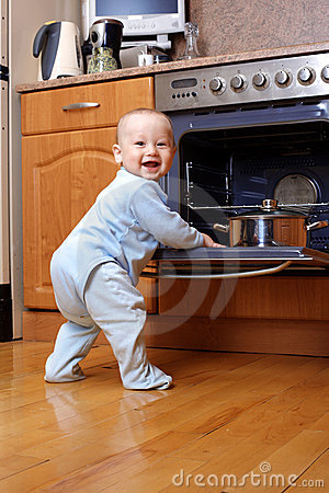 Funny baby at stove