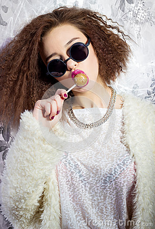 Free Funny Beautiful Sexy Girl In Glasses And A White Coat Licks A Candy Bar, Bright Makeup, Fashion Photography Studio Stock Photo - 48770450