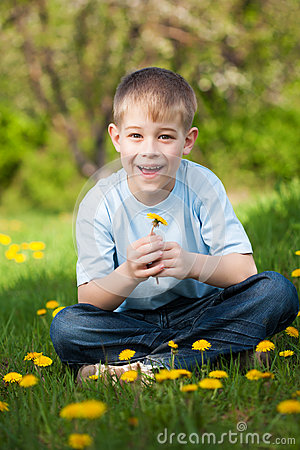 Funny boy with dandelions in a green park. summer