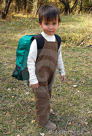Funny boy stands with backpack