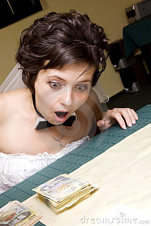 Funny bride looking at stack of mo