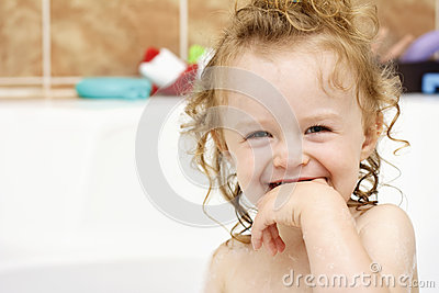 Funny cheerful toddler cleaning teeth in the bath