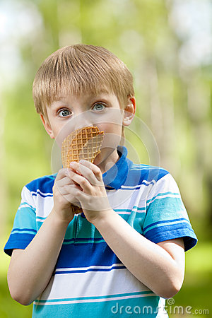 Funny child eating a tasty ice cream outdoors