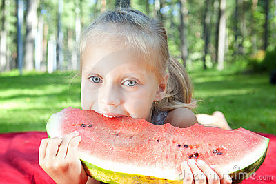 Funny child eating watermelon in the park