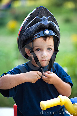 Funny child putting helmet