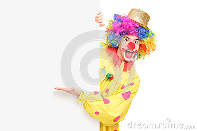 A funny circus clown posing behind a panel and gesturing