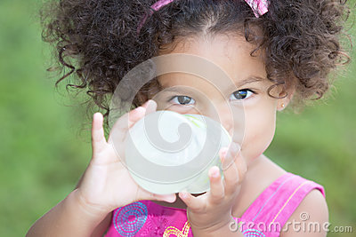 Funny And Cute Latin Girl Drinking From A Baby Bottle