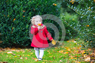 Funny cute toddler girl in red coat in autumn park