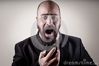 Funny elegant bearded man screaming on the phone