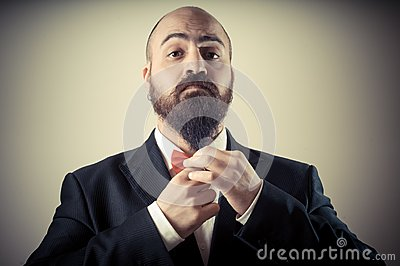 Funny elegant bearded man touching beard