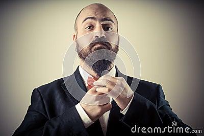 Funny elegant bearded man touching beard