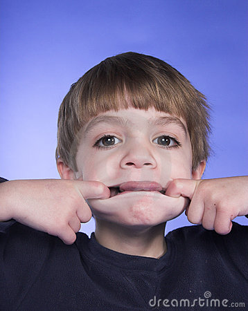 funny face. A young boy makes a funny face