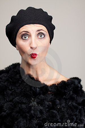 Funny face of mature woman in fur on gray