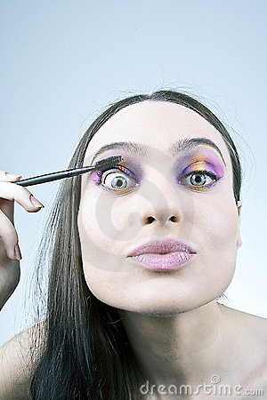 Funny girl applying mascara