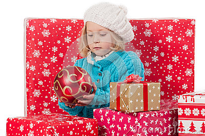 Funny girl around christmas boxes with red ball