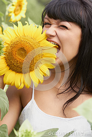 Funny girl biting a sunflower
