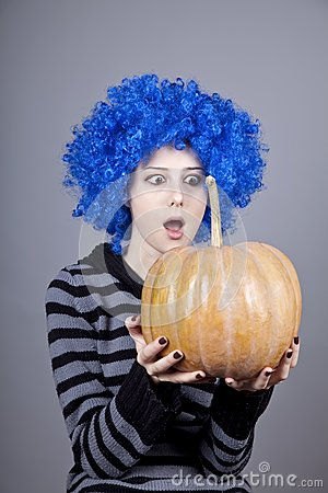 Funny girl with blue hair keeping pumpkin.