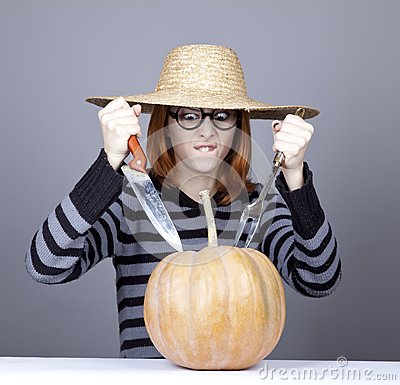 Funny girl in cap try to eat a pumpkin.