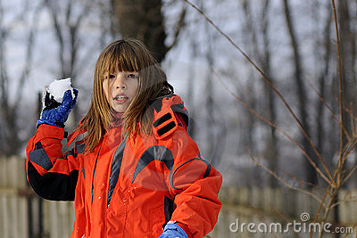 Funny girl fighting with snowballs