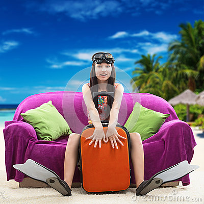 Funny girl with her luggage, tropical beach background