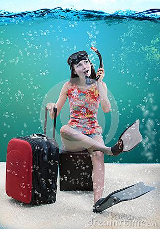Funny girl with her travel luggage sitting under the sea