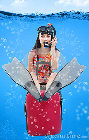 Funny girl with her travel luggage sitting under the water