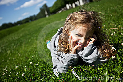 Funny girl lies on the green grass