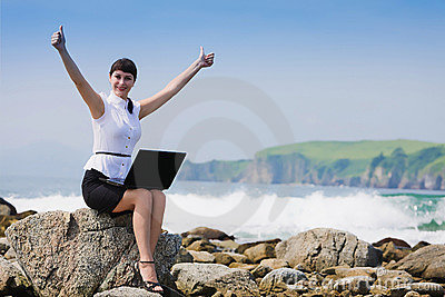 Funny girl on the rocky shore sits