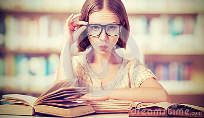 Funny girl student with glasses reading books Stock Photo