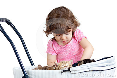 Funny kid girl playing with small kitten