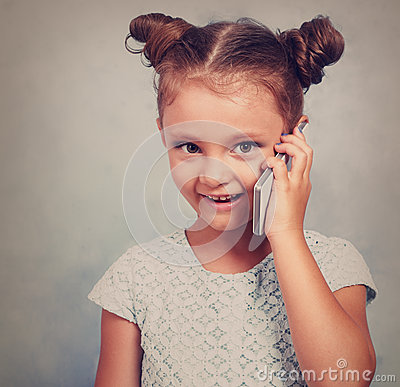 Free Funny Kid Girl Talking On Mobile Phone With Happy Smile On Blue Stock Photos - 79495493