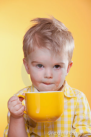 Funny little boy drinking from big yellow cup