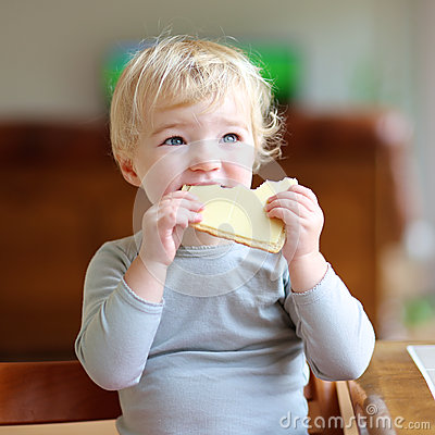 Free Funny Little Girl Eating Sandwich At Home Stock Photos - 44865243