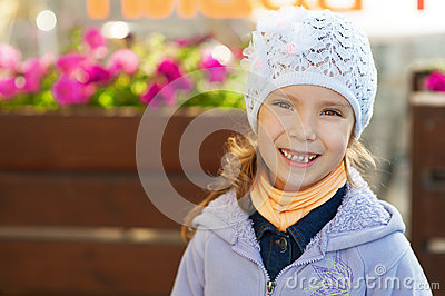 Funny little girl in jacket and hat