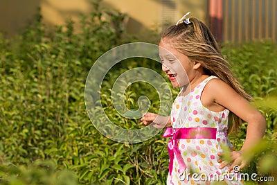 Funny little girl running in the park