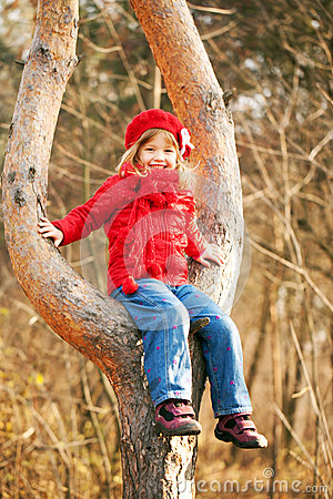 Funny little girl sitting on tree and smiling