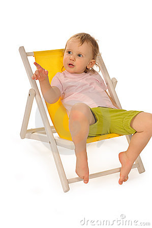 Funny little girl in studio on yellow deckchair
