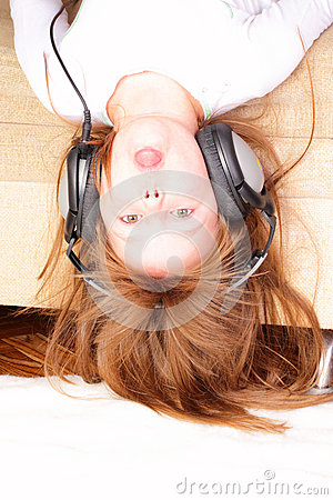 Funny little girl upside down with headphones
