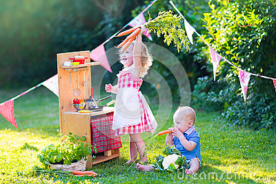 Funny little kids playing with toy kitchen in the garden