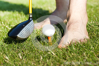Funny male feets playing with golf ball