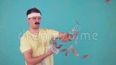 Funny man with a mustache throws money and looks at the camera. Slow mo blue isolate background stock footage