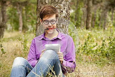 Funny men with glasses doing homework at the park