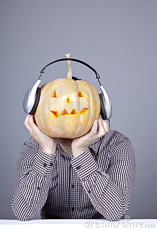 Funny men with pumpkin and headphone.