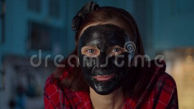 Funny 30s woman with black cosmetic mask on her face making grimace at home looking at camera. Woman making funny faces. Funny 30s woman with black cosmetic mask stock video footage