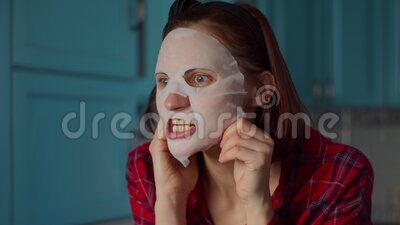 Funny 30s woman with white cosmetic mask on her face making grimace at home. Woman making funny faces in mask on blue. Funny 30s woman with white cosmetic mask stock video footage