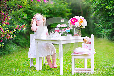 Funny toddler girl playing tea party with a doll