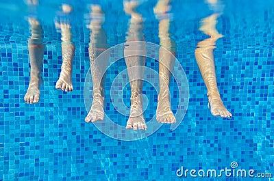 Funny underwater family legs in swimming pool